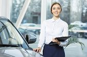 image of showrooms  - Young pretty woman dealer in showroom standing near car  - JPG