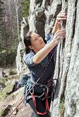picture of climbing wall  - Portrait of a beautiful young woman climbing difficult wall - JPG