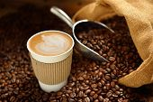 stock photo of latte coffee  - Paper cup of coffee latte and coffee beans on wooden table - JPG