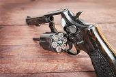 stock photo of revolver  - black revolver gun with bullets isolated on wooden background - JPG