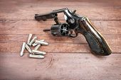 foto of revolver  - black revolver gun with bullets isolated on wooden background - JPG