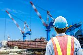 foto of shipbuilding  - construction worker checking location site with crane on the background  - JPG