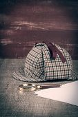 image of private investigator  - Deerstalker or Sherlock Hat and magnifying glass on Old Wooden table - JPG