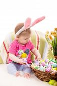stock photo of baby easter  - Baby girl with bunny ears choose easter eggs from basket - JPG