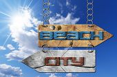picture of directional  - Wooden directional sign with two arrows in opposite direction hanging with metal chain with text beach and city on blue sky with clouds and sun rays - JPG