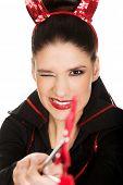 foto of blinking  - Beautiful woman in devil carnival costume blinks eye - JPG