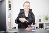 foto of grocery cart  - Smiling Businesswoman in Black Suit Pointing at Small Toy Grocery Cart on Top of her Desk While Looking at the Camera - JPG