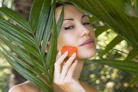 picture of papaya fruit  - Beautiful caucasian woman having fresh papaya natural facial mask apply skin care and wellness - JPG