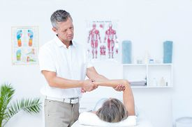 pic of physiotherapist  - Physiotherapist examining his patients arm in medical office - JPG