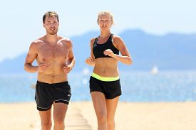 stock photo of cardio exercise  - Fitness running couple exercising cardio on beach - JPG