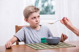 stock photo of fussy  - Poor eater refusing to eat milk with cereal - JPG