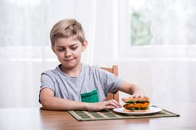 picture of fussy  - Image of fussy kid with chicken sandwich - JPG