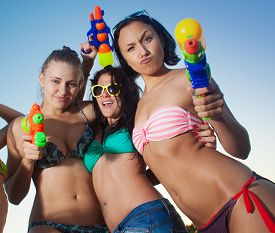image of pistols  - three young girls  playing and posing with water pistols on the beach  - JPG