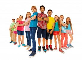 stock photo of dominate  - Group of dominate looking children boys and girls stand together with closed hands and look down confidently isolated on white - JPG