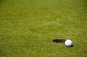 Golf ball zeer dicht bij een gat op een putting green