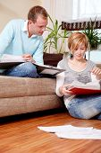 Scenic young family couple at home indoors in living room doing paperwork sitting on couch and floor