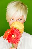 Portrait of blond smiling woman with yellow red flower enjoying the spring