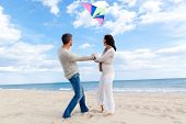 Happy outdoor autumn winter spring couple embracing and running on beach  a kite fly