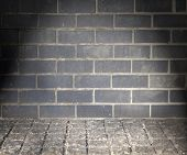 Grungy furnice like wall and floor with black brick and cobble stone.