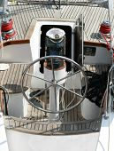 Rudder, compass and captain's hat on wooden yacht