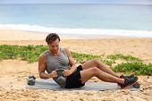 Russian Twist - Fitness man exercising on beach training with kettlebells working out core, obliques poster