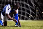 Male soccer player tying shoelace against goal post on soccer field poster