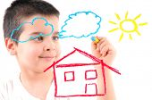 Adorable 6 years old boy painting a house, sun and clouds on glass. White background high resolution