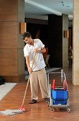 stock photo of housekeeping  - Young housekeeper mobbing the floor  - JPG