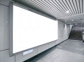 Blank billboard in underground passage to subway