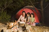 mother and two daughters sitting in front of a campfire