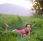 pic of tall grass  - young girl lying down in the tall grass - JPG
