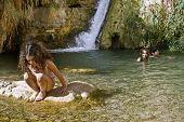 Three kids swimming in an oasis pool with waterfall