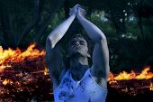 Dramatic twilight portrait of young emotional man with hands up praying in front of fire (slight nig