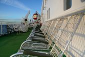 Onboard cruise of the liner. Anybody still no on a deck. Early morning. The metal armchairs for rest wait for the people. The day will be solar and perfect.