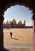 Muslim man looking at main prayer hall and courtyard of Badshahi Mosque, Lahore, Pakistan