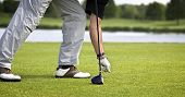 Male golfer arranging tee with ball to tee off.
