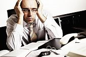picture of sad man  - Worried businessman sitting at office desk full with books and papers being overloaded with work - JPG