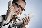 Stressed unhappy telephonist in call center wrapped with phone cables being over-strained with work,