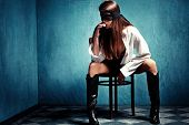 sensual young woman with lace covering eyes sit on chair in shirt and leather boots