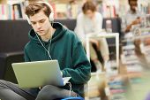 Serious Hipster Student Boy Listening To Music In Headphones And Using Laptop While Searching For In poster