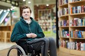 Content Handsome Young Disabled Student With Headphones On Neck Siting In Wheelchair And Looking At  poster