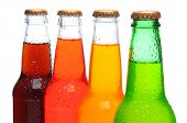 Closeup of four assorted soda bottles with condensation. Horizontal format over a white background.
