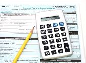 picture of income tax  - calculator and pencil over a canadian general tax return form - JPG