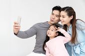 Candid Of Young Attractive Happy Asian Family Using Smartphone Selfie Together Or Video Call. Social poster