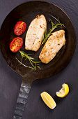 picture of pangasius  - fish fillet fried with fresh herbs in a pan - JPG