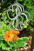 stock photo of windchime  - cross windchime with plants daisy closeup peace - JPG