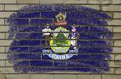 Bandera de grunge de nosotros del estado de Maine en pared de ladrillo pintada con tiza