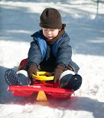 The Boy Sits On A Sled
