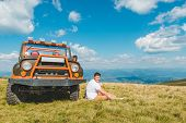 Man Sitting Near Suv Car At The Top Of The Mountain With Beautiful View. Travel Concept poster