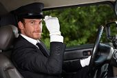 Confident chauffeur sitting in elegant automobile.?